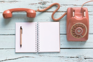 The diary blanks with retro telephone on the wooden table
